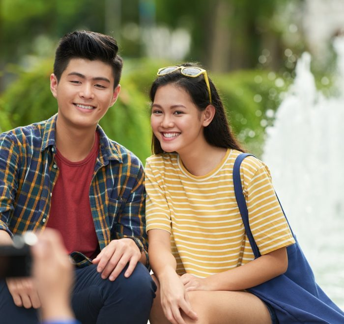 Joyful young Vietnamese couple posing for photographer
