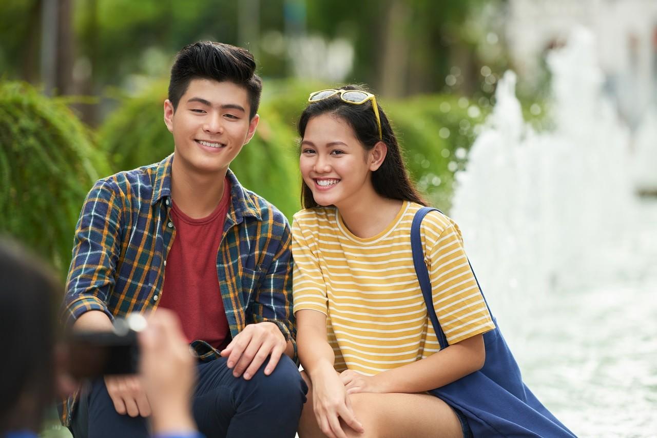 Joyful young Vietnamese couple posing for photographer