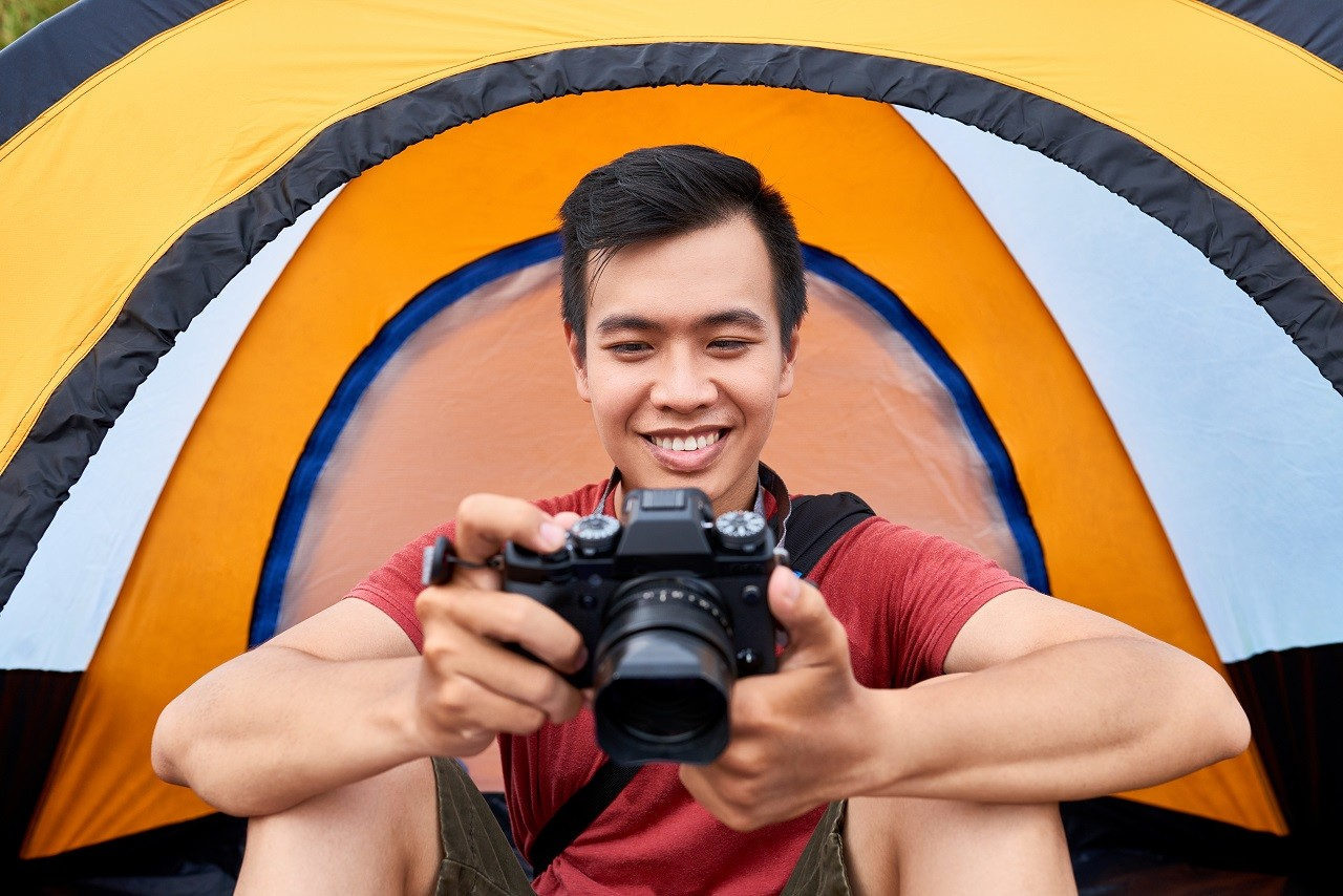 Cheerful Vietnamese traveler sitting in his tent and checking photos on digital camera